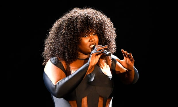 A dark-skinned woman with a large, curly, relaxed afro stands on stage in a black bodysuit with patterned cutouts. She holds a microphone up to her lips and gestures with her free hand.