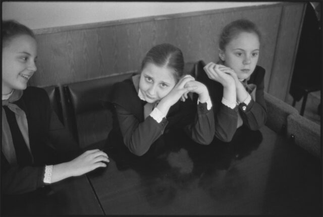 A black-and-white photograph of three light-skinned schoolgirls in dark, long-sleeved, matching uniforms. The girl on the right stares off, hands clasped by her cheek; the girl in the middle stares at the viewer with her head on her hands; and the girl on the left is laughing.