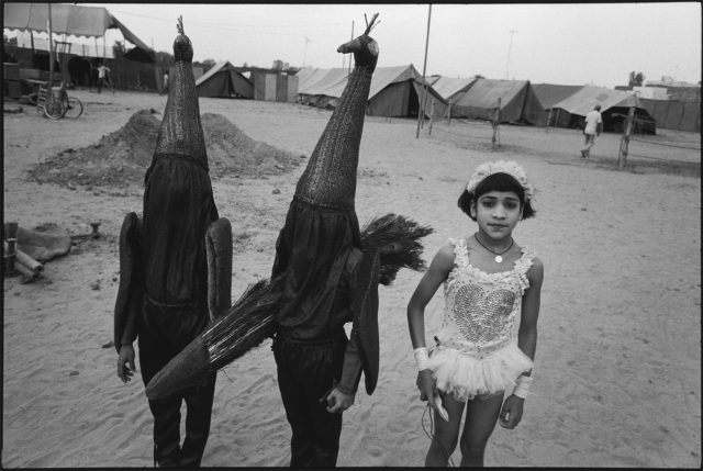 A black-and-white photograph of a medium-skinned girl in a frilly acrobat costume standing next to two children in identical, full-body peacock costumes. One peacock-costumed child holds a bundle of long peacock feathers, and they all stand on sand with a row of tents behind them.