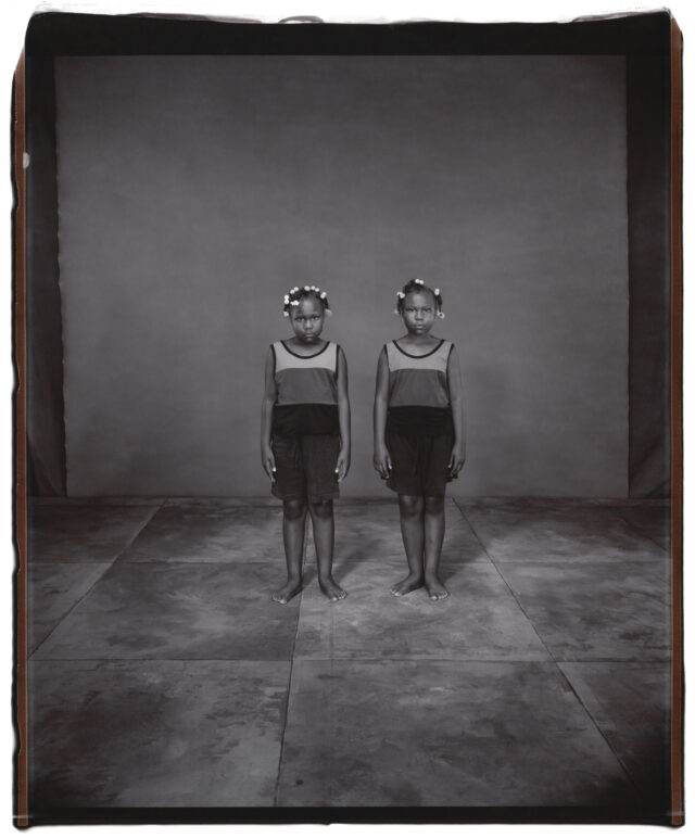 A black-and-white photograph of young twin girls standing next to each other. Both girls have dark skin and dark hair with white beads tied into it. They both wear striped tank tops and dark shorts. They stand straight with their arms by their sides, both staring into the camera with serious expressions.