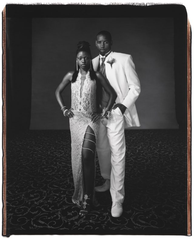 A black and white photograph of a teenage couple in formal clothing. A teen girl with dark skin and straight, dark hair stands slightly in front of a teen boy with dark skin and shortly cropped dark hair. She wears a long, light colored lace dress with a slit on the leg, and a jeweled chain wrapped around her thigh. He wears a white suit with a dark tie.