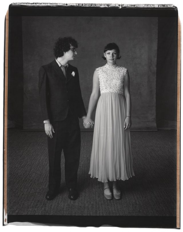 A black and white photograph of a teenage couple in formal clothing standing side by side, holding hands. The boy has light skin and short, dark, curly hair. He wears a dark colored suit with a white boutonniere. He turns his head to look at the girl, who also has light skin and short, dark, straight hair and wears a light colored, ankle length dress.