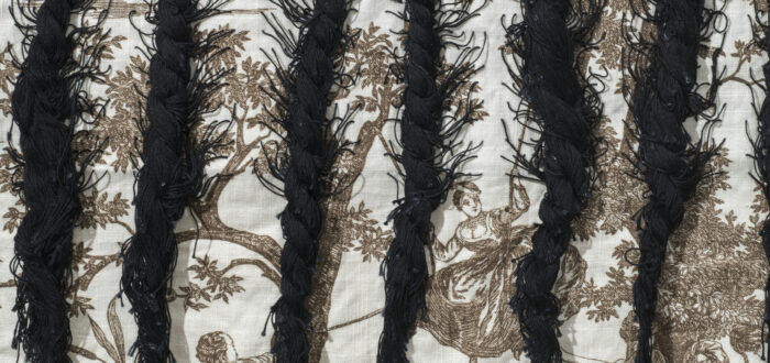 A close up photograph of braided black hair woven into cloth featuring colonial narrative scenes.
