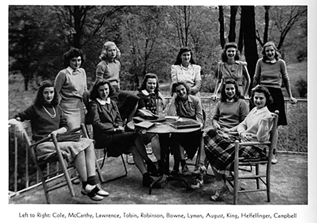 Eleven young light-skinned women pose on a patio for a group portrait. Some sit around a table covered with books; others stand leaning against a railing.