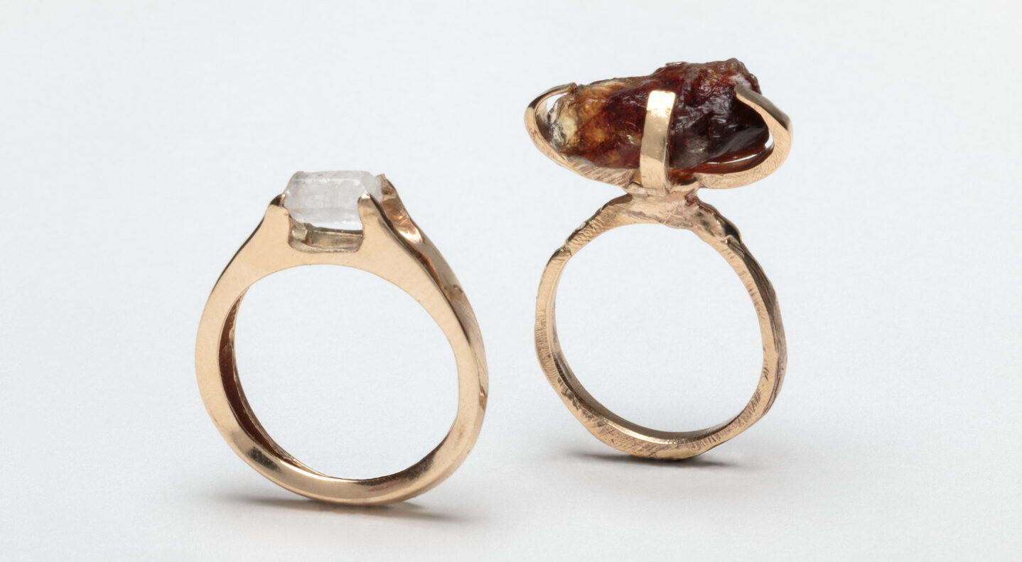 Two rings with gold bands and small gem-like forms on top. The gems are crafted from raw sugar. The left ring is perfectly circular with a small, smooth, white sugar crystal on top. The right ring is a slightly rougher circle, with a larger, lumpy, brown sugar crystal on top.