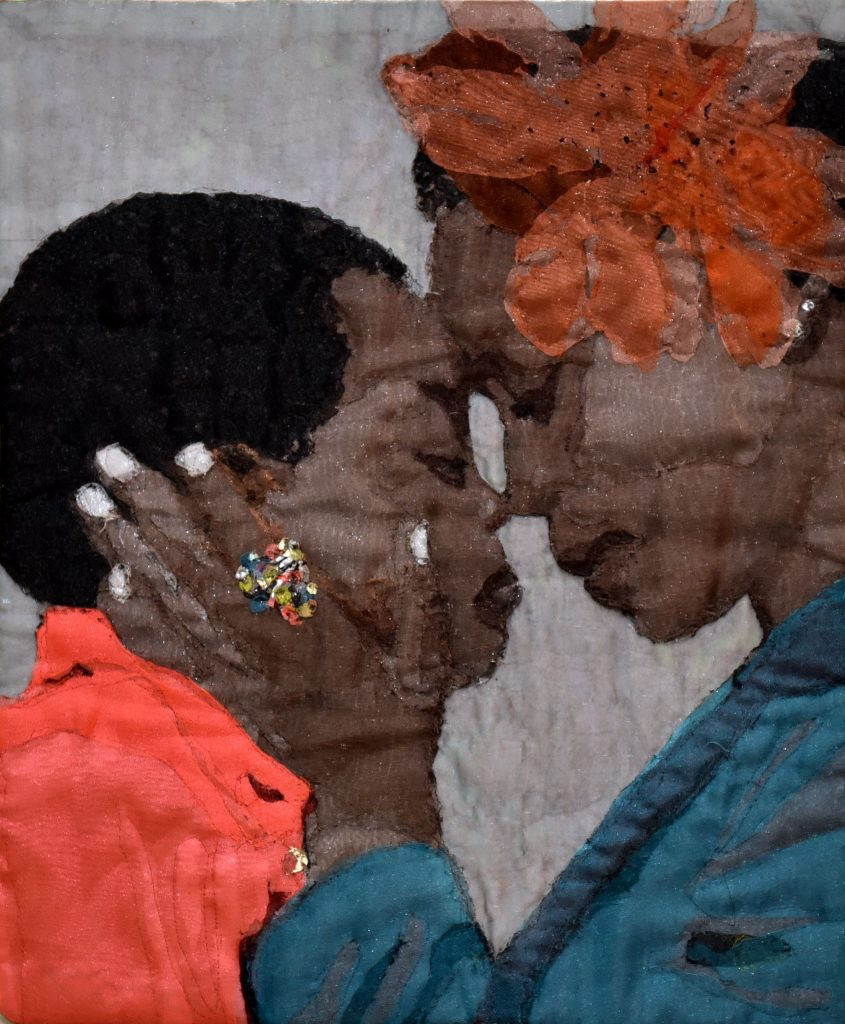 An image sewn as a quilt of a dark-skinned woman, wearing a large orange flower in her hair, holding the face of a dark-skinned child in her hands as they touch their foreheads and noses together lovingly.