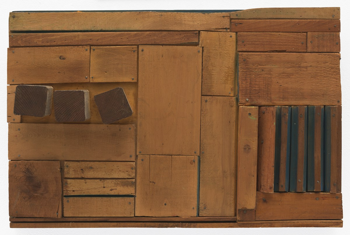 A wooden sculpture featuring brown, horizontal slabs cut in different lengths and widths atop which three square blocks are affixed in the left side, and the crevices of some of the slats are painted blue on the right side.