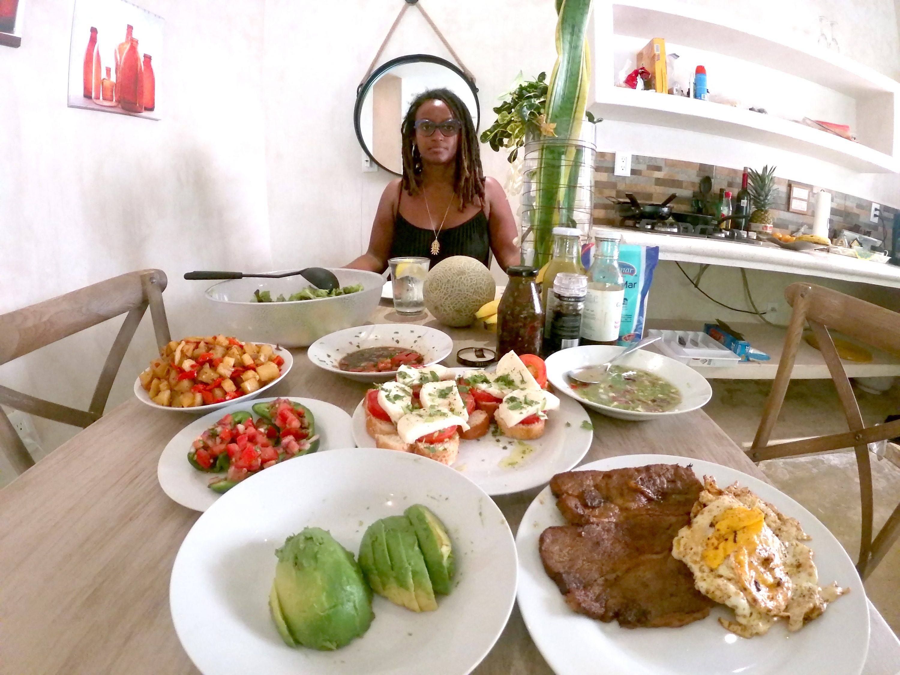 A medium-dark skinned adult woman sits at the end of a table, as if sitting across from the viewer. She has shoulder-length, dreadlocked hair, and wears glasses and a black tank top with a gold necklace. The table is set with colorful foods like avocados and bruschetta.