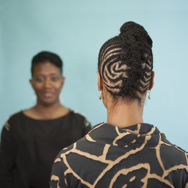 A color photograph featuring two dark skinned women in front of an aqua background. The woman on the left faces the camera. She is wearing a black shirt with gold details on the shoulders and has her brown hair pulled back. The woman on the right stands with her back to the camera wearing a black and tan patterned shirt. Her brown hair is braided in an elaborate pattern and pulled up on top of her head.