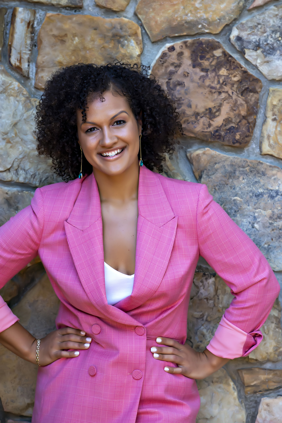 A medium-skinned woman with tight, chin-length black curls stands against a stone wall wearing a pink blazer with a low-cut neckline. She rests her hands on her hips and smiles warmly at the camera.