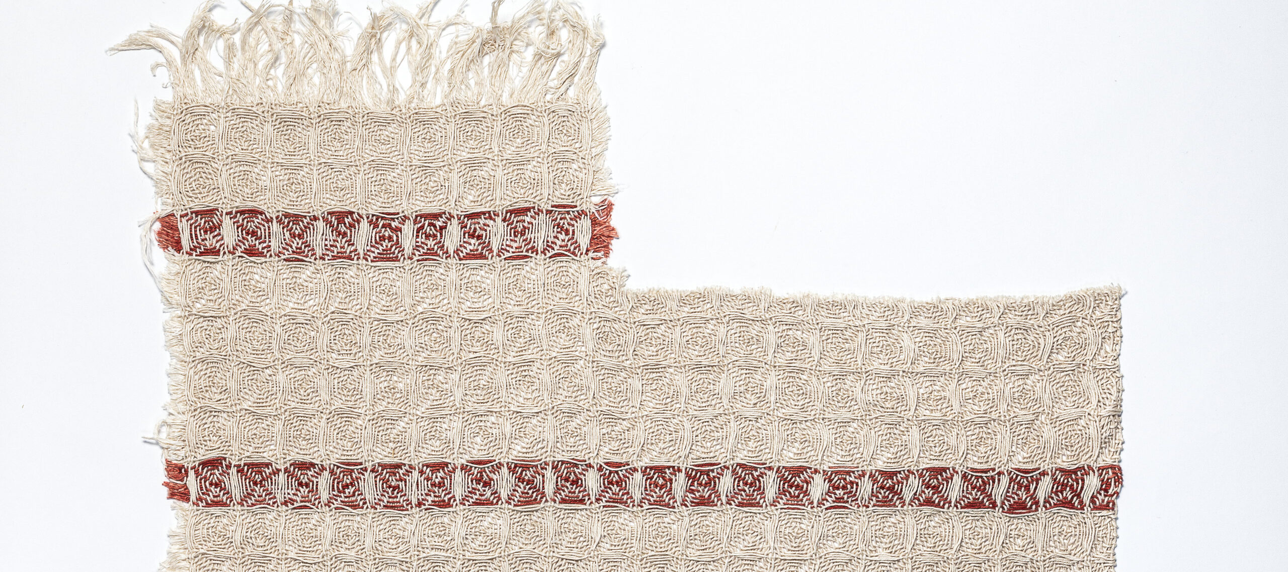 A white, linen dishtowel with three equidistantly parallel horizontal red stripes, frayed edges, and a missing rectangular section in the top right corner. The bottom has been mostly untangled and long, frayed threads hang loosely.