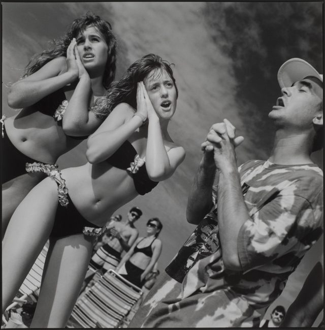 A black and white photograph of people singing and dancing outdoors. In the foreground on the left of the frame, two young girls wearing matching black bikinis pose with open mouths and their hands on their right cheeks. On the right of the frame, a young boy stands with his eyes closed and mouth open, clasping his hands at his chest.