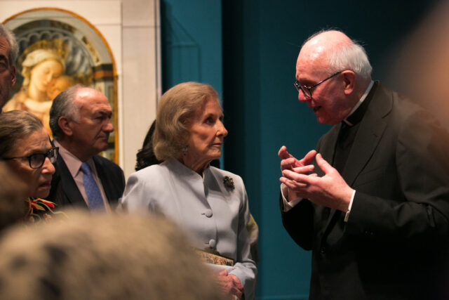 A group of light-skinned older people stand close in an art gallery listening as a Monsignor speaks to them. In the background is an artwork depicting Mary and Jesus; the wall next to it is painted teal.