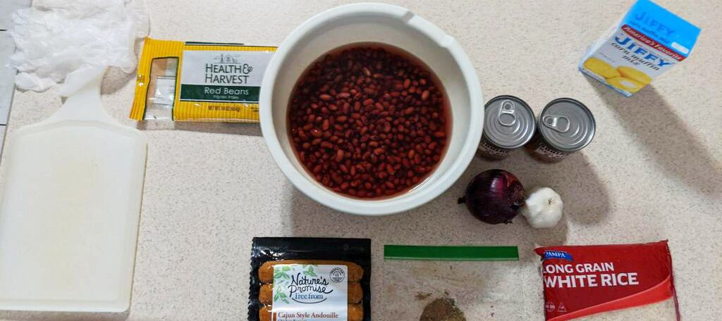 An aerial view of a white countertop with a bowl of red beans and other ingredients laid out on it, including a couple of cans, onion, garlic, a bag of rice, a box of corn muffin mix, and sausages.