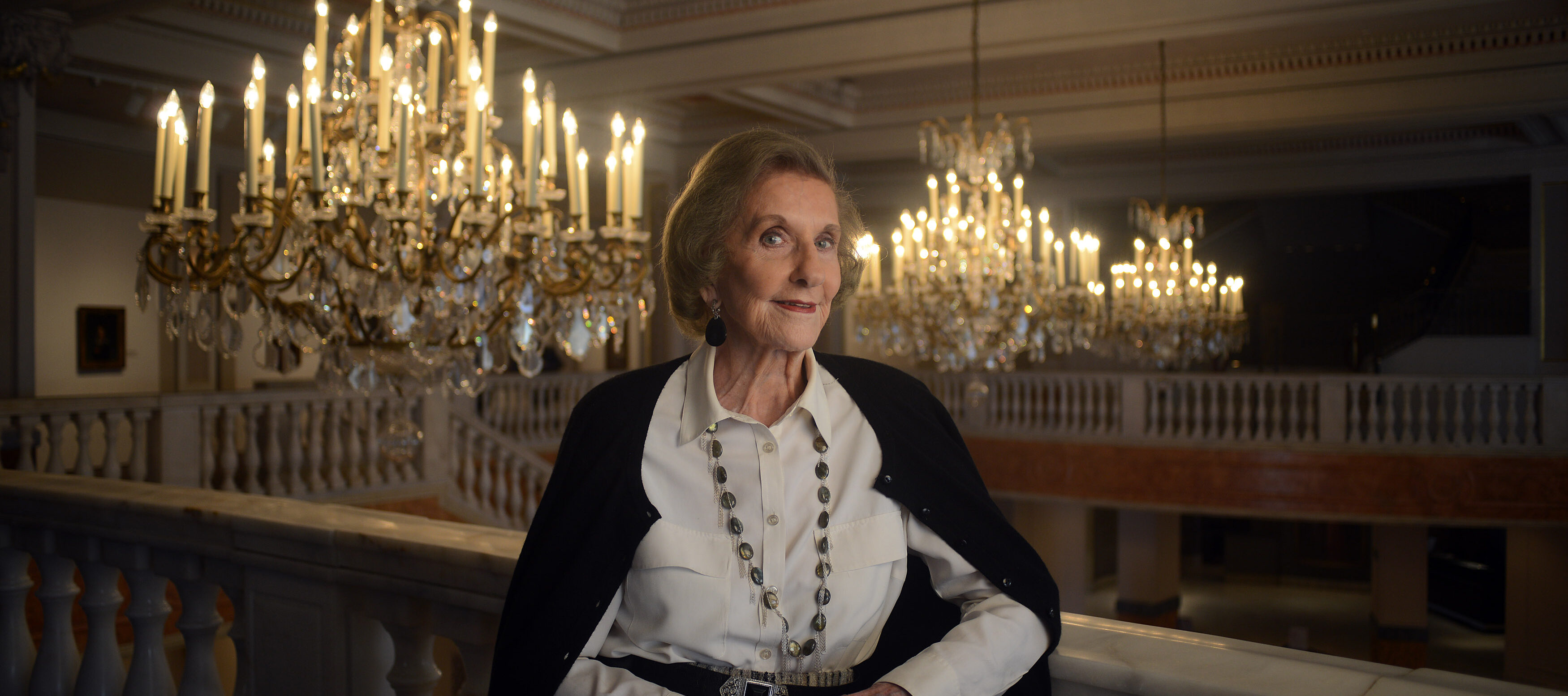 A light-skinned older woman in a collared white shirt and black cardigan leans against a railing with a slight smile. Ornate chandeliers can be seen behind her.