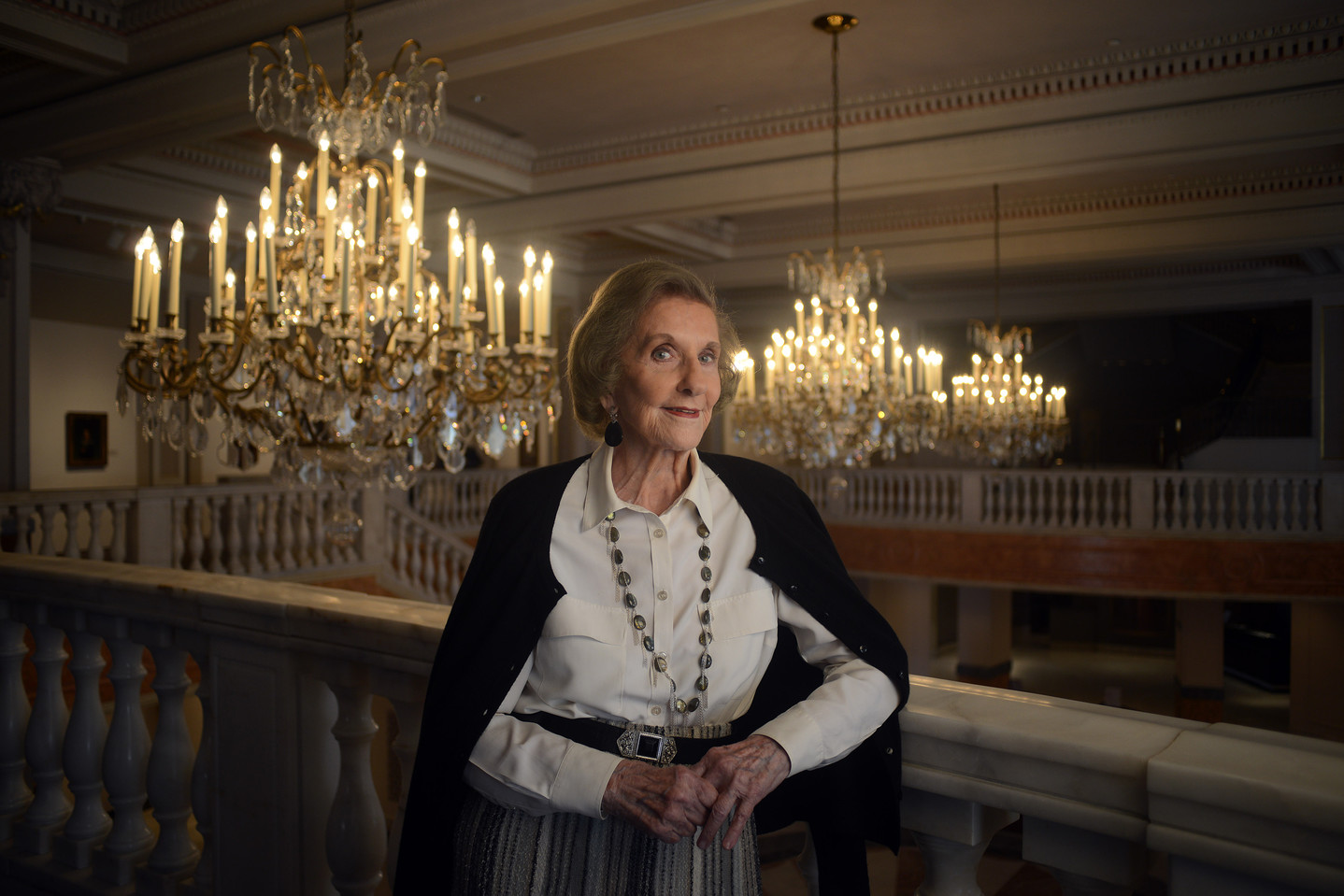 Wilhelmina Cole Holladay leans against a railing with a slight smile. She is a light-skinned, older woman with short, gray hair, and she wears a collared white shirt and black cardigan. Ornate chandeliers can be seen behind her.