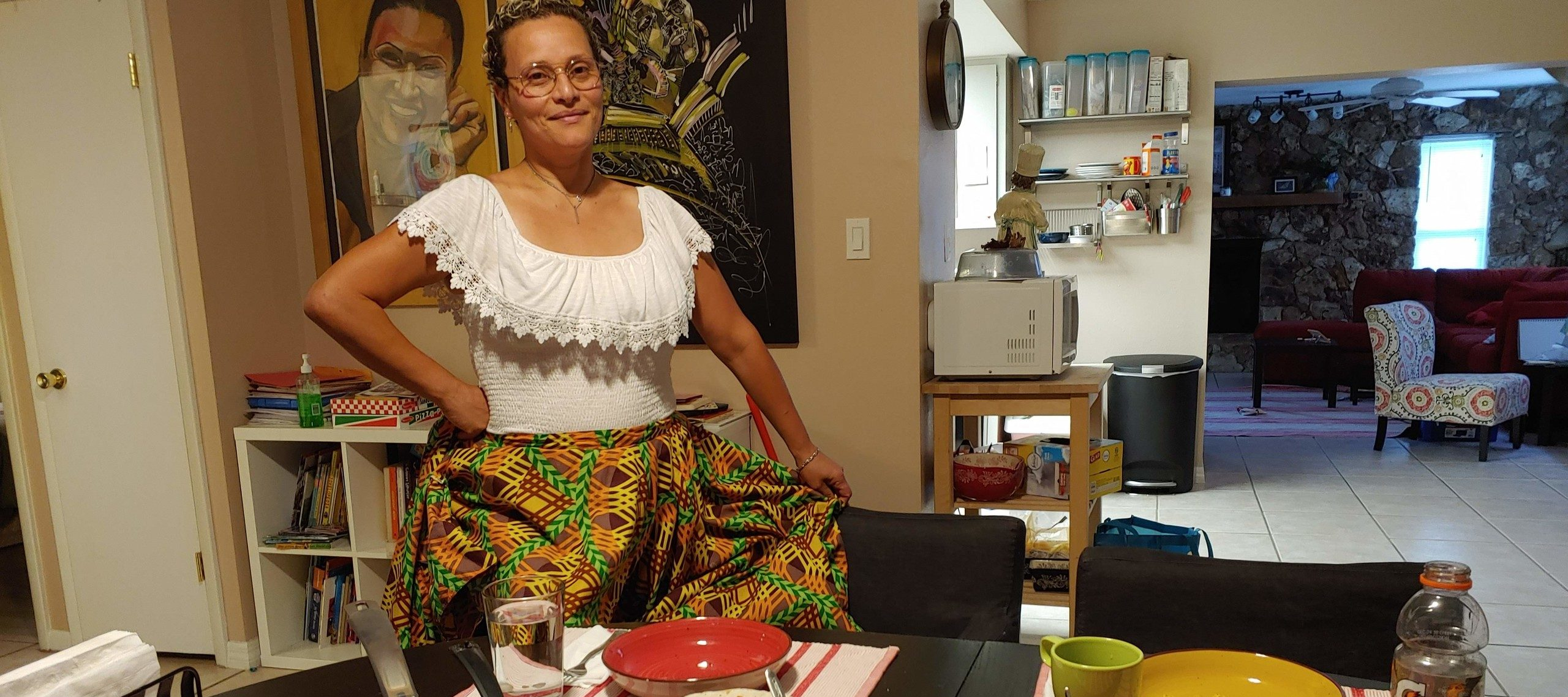 A medium skin-toned adult woman wearing traditional Puerto Rican dress—a white blouse with lace neck and brightly patterned skirt—stands smiling in front of her dining table in her home. The table is set with bowls and pots of ground beef, salsa, sauce, guacamole, and salad.