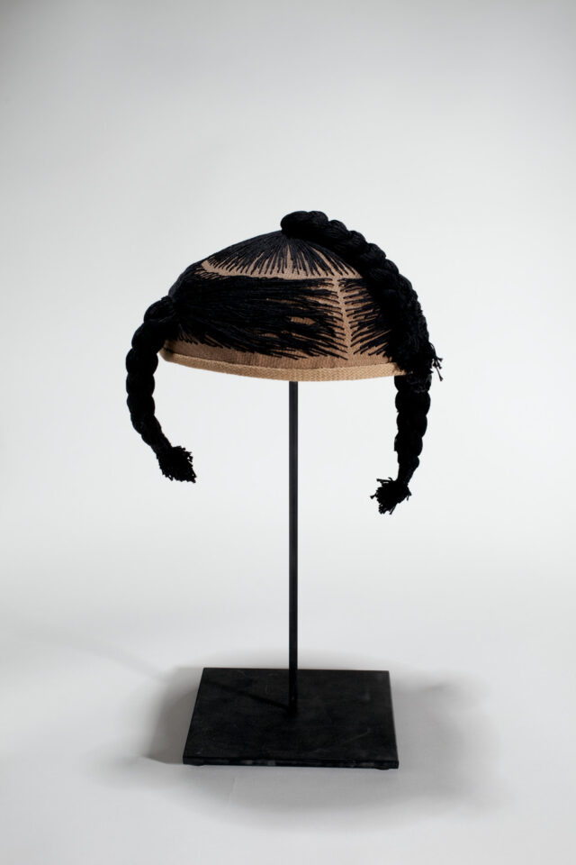 A wig cap sits mounted on a black stand. Black thread is stitched into the cap, mimicking hair. The thread forms three braids.