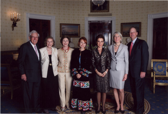 A formal photograph of seven light-skinned individuals—four women in the center, two men on either end—in the U.S. Presidential office. The woman in the very middle wears a traditional Mexican dress, to her left another woman wears a cheetah-patterned skirt and blazer set. The others are in various business dress. Everyone smiles at the camera.