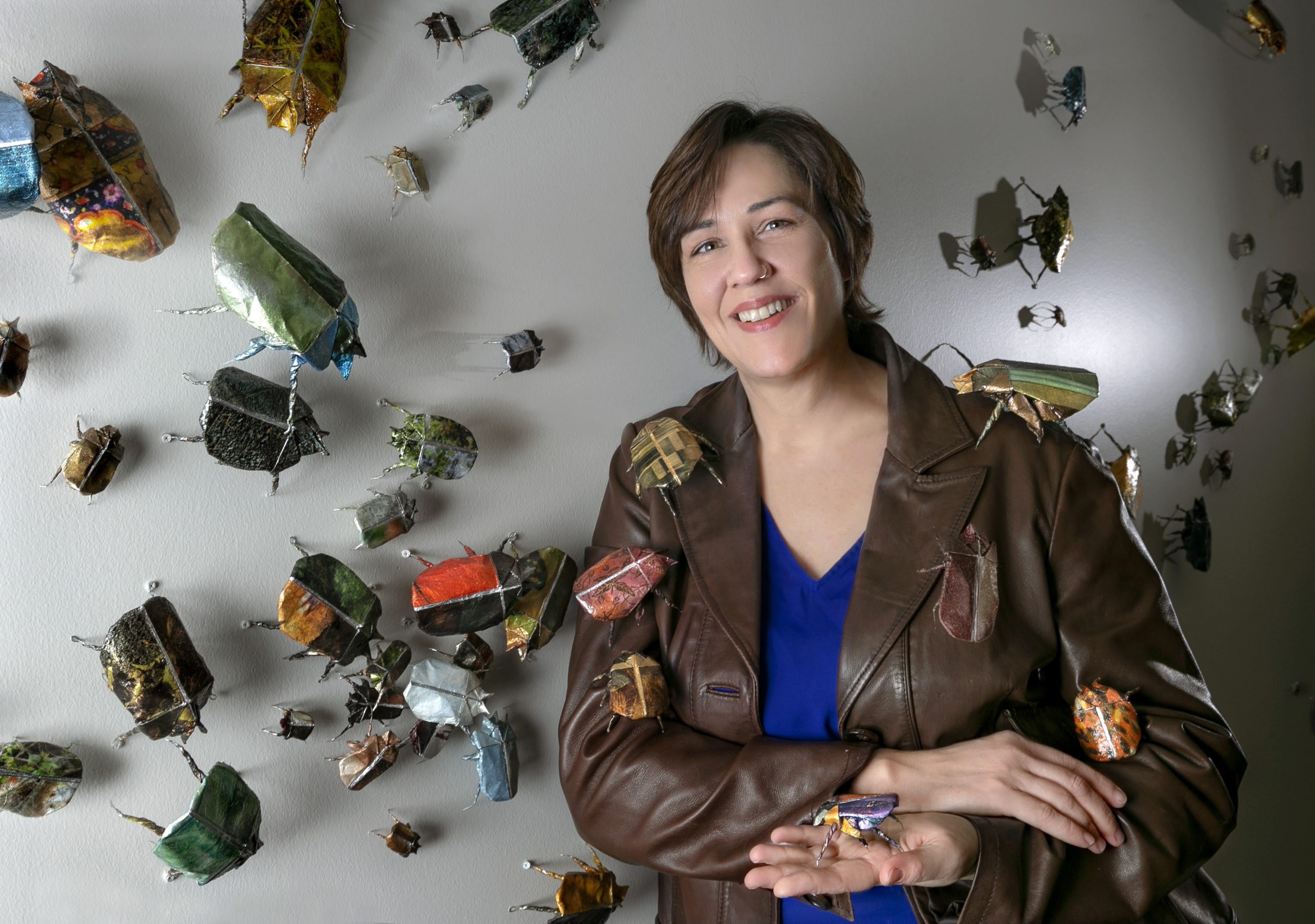 A light-skinned woman with short brown hair stands in front of a white wall to which paper beetles, sculpted out of photographs, are affixed. The woman holds a beetle in her open palm, while others are arranged atop her brown leather jacket. She smiles slightly at the camera while leaning against the wall.