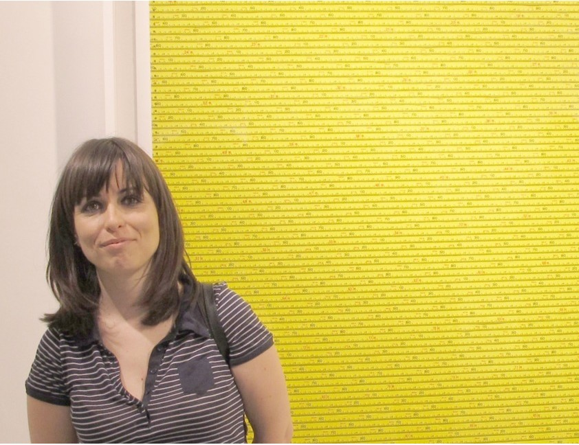 A medium-skinned woman stands in front of a bright yellow artwork. She has shoulder-length straight brown hair with bangs and wears a striped t-shirt. She smiles slightly.