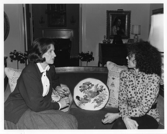 Two light-skinned women sit on a couch in a residence. The woman on the left wears a cardigan, blouse, and skirt and has chin-length straight brow hair. The woman on the right has curly shoulder-length hair, wears glasses, and a polka dotted top and black pants. They look at each other as they are in conversation. Four embroidered pillows sit on the couch behind and next to them.