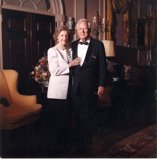A light-skinned elderly couple formally pose for a photograph in an ornate room. They wear formal evening attire and smile subtly. The woman places her hand against the man's lower chest.