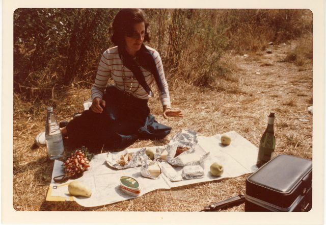 A vintage photograph of a light-skinned woman with short brown hair sitting on the ground with a map spread out in front of her. On top of the map is a picnic with apples, potatoes, radishes, sandwiches, a bottle of water, and a bottle of wine. There is a small black case in the bottom right corner of the photograph.