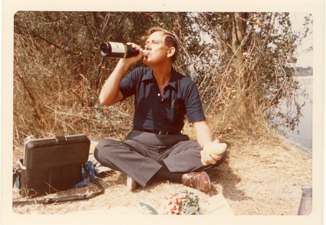 A vintage photograph of a light-skinned man with short light-colored hair sitting on the ground. The man drinks out of a full sized bottle of wine with a potato in his other hand. There is a small black case beside him and a bunch of radishes sitting on a map in front of him.