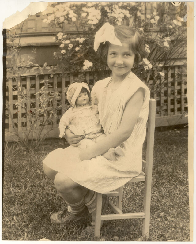A sepia-toned photograph of a young light-skinned girl sitting outside in a chair, smiling and cradling a doll. She wears a light color dress with a large bow in her hair. Behind her is a lattice and flowering plants.