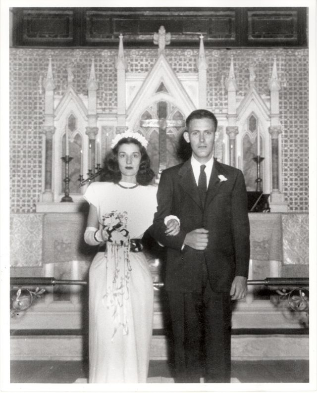 A black-and-white wedding portrait features a light-skinned, slim couple standing in front of an ornate altar. The woman clasps her husband, clad in a suit, at the elbow and holds a bouquet. Neither smile.