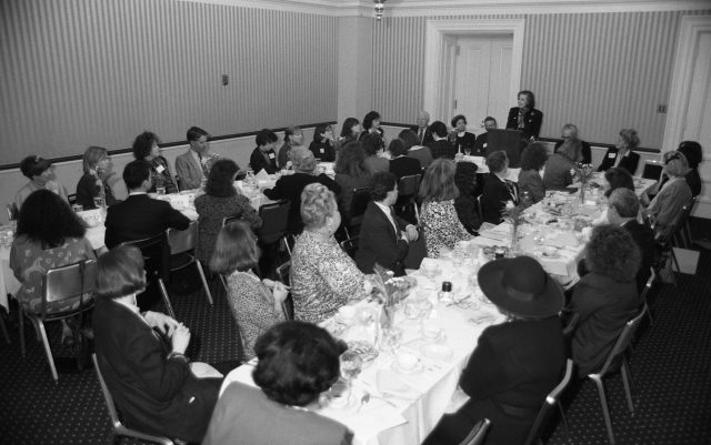 A black and white photograph of a room full of men and women seated at two long tables. In the front of the room a light-skinned woman with short brown hair stands at a podium addressing the group. The men are wearing suits and the women are wearing formal luncheon attire from the 1980s.