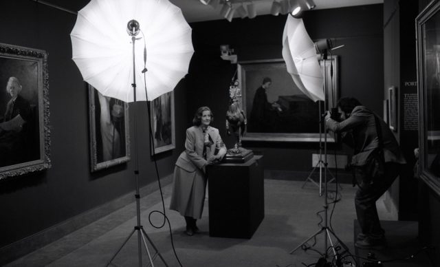 In an art gallery featuring five large oil paintings on the walls, a male photographer takes a posed photograph of a light-skinned woman leaning against a podium in the center of the room. It holds a sculpture of a man on a horse. The woman smiles slightly under the photographer's large umbrella lights. She wears a blazer, long skirt and an elegant silk scarf tied around her neck.