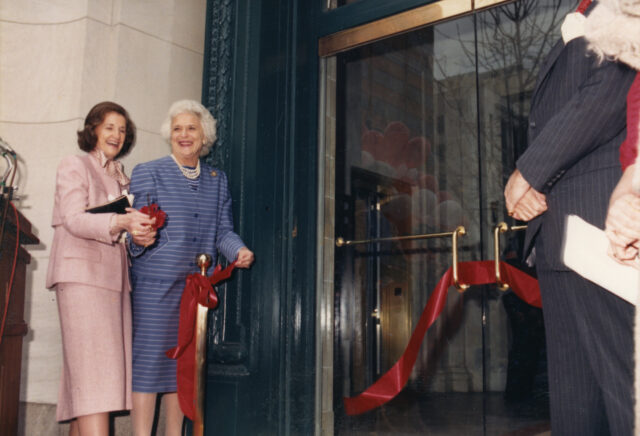 Two older light-skinned women in suit and skirt sets smile and cut a red ribbon on the doors of an institution. One woman has brown hair and the other hair white hair.