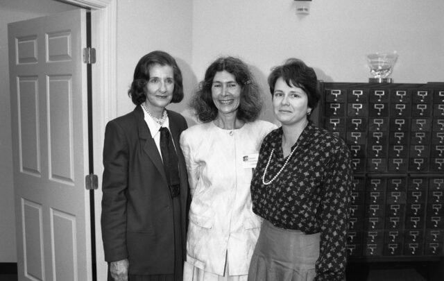 Three light-skinned women stand in a row smiling. They all have short to medium-length dark hair and wear 1980s-style business wear. Two wear pearls. In the background is a wooden library card catalogue.