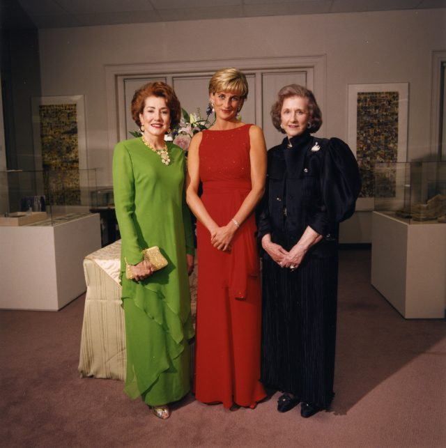 Three light-skinned women stand next to each other in fancy evening dresses inside an art gallery. The woman on the left wears a green dress, has red hair, and clasps a purse in her left hand; the women in the middle has short blonde hair, wears a red dress, and clasps her hands together in front of her; the women on the right has greying brown chin-length hair and wears a black dress, and also clasps her hands together in front of her. They all smile at the camera.