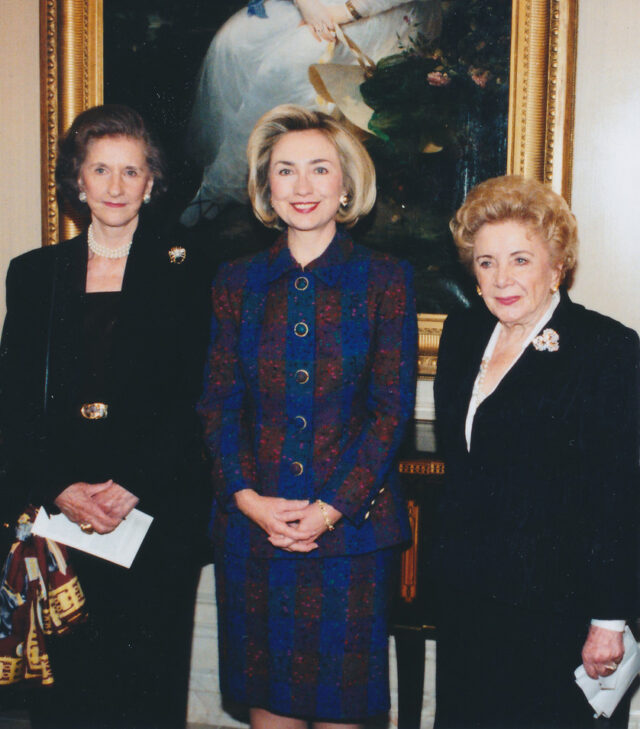 Three light-skinned women wearing formal skirt and blazer sets stand in a row smiling for a photograph. A woman with blonde hair wears a blue and red/orange striped suit, while the others are all in black with different broaches adorned on their left lapel