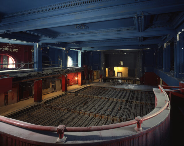 A large, ornate hall is photographed from a balcony, looking down onto a floor under renovation, with steel supports in place. Around the hall paint chips off of the walls and a layer of dust coats the balcony railing. Construction debris is visible on the left side.