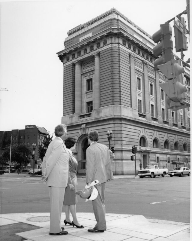 A black and white photograph of two light-skinned men and a light-skinned woman dressed in suits from the 1980s stand across the street from an ornate five-story stone building. The figures glance up a the building.