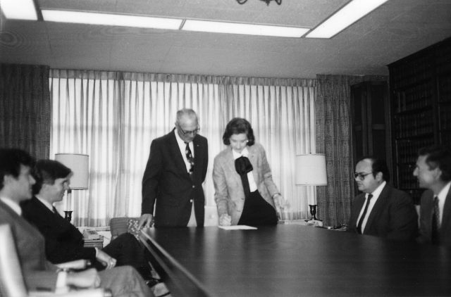 At the head of a large board table, a light-skinned woman stands next to a light-skinned man, both wearing business attire. Four other men sit at the table looking at the man and woman. The woman leans down slightly, signing a document with her right hand.
