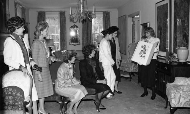 A group of light-skinned women in an ornate residential living room. One woman holds up a large book of illustrated prints and talks to the group. The other women look on with expressions of happiness and intrigue.