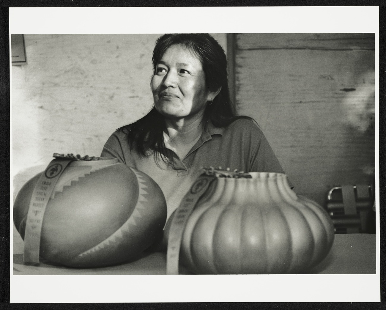 A black-and-white photo of a Native American woman with dark, long hair. She sits at a table with two large pieces of pottery in front of her, each has a winner ribbon on it. She looks off to the left smiling slightly as sunlight illuminates her face.