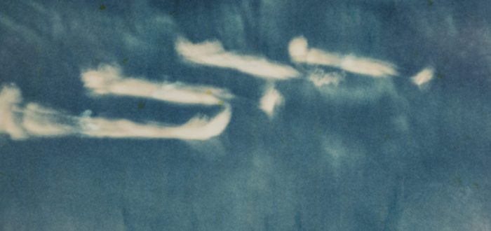 Four long, white, cloudy-looking wisps against a cyan navy background.