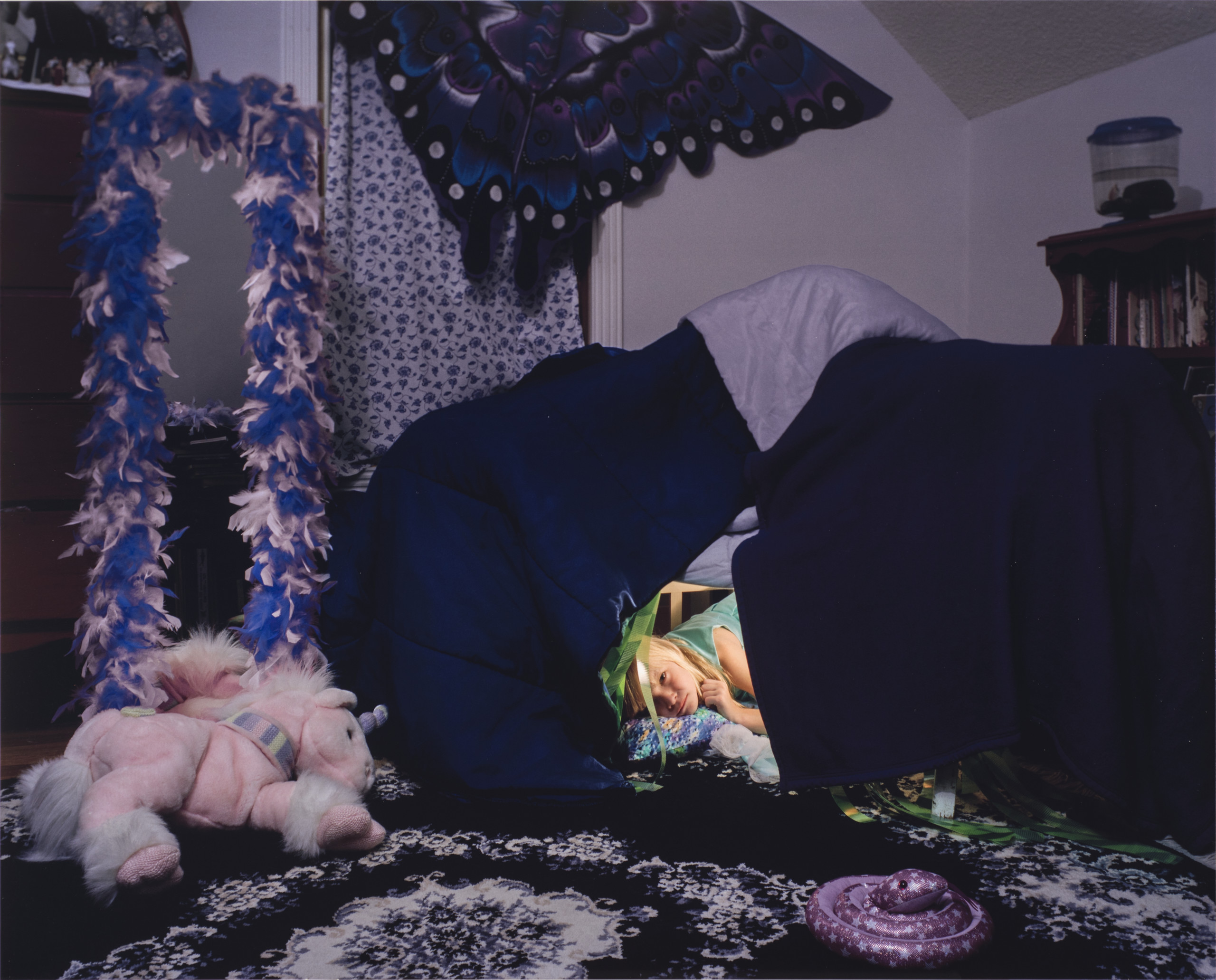 A color photograph of a young light skinned girl with light blonde hair. The girl peeks out from a fort made from a dark blue and purple comforter. A light pink and purple stuffed unicorn sits on a purple and white floral rug in front of the fort. A purple, blue, white, and black paper butterfly-shaped kite hangs on the wall above the fort.