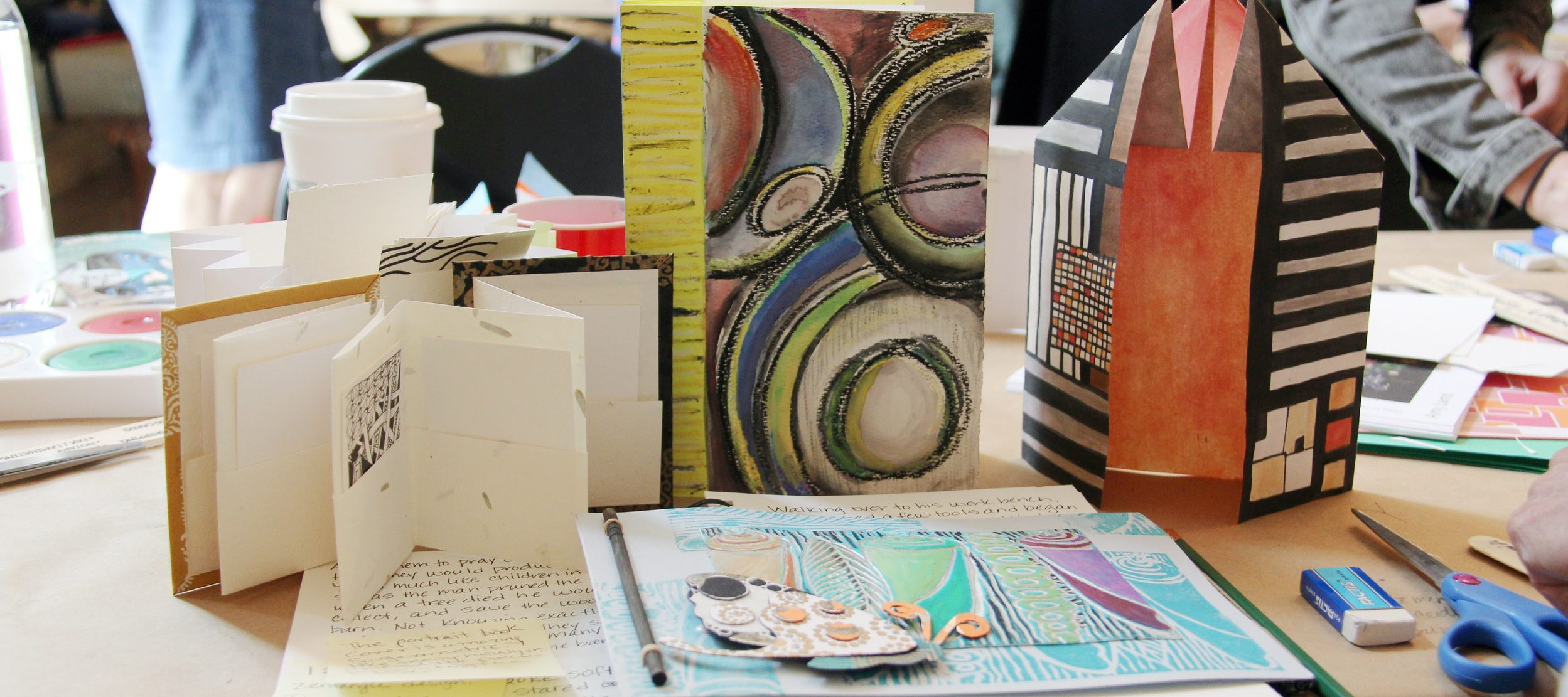 An assortment of artist books with various paper folds and artworks.