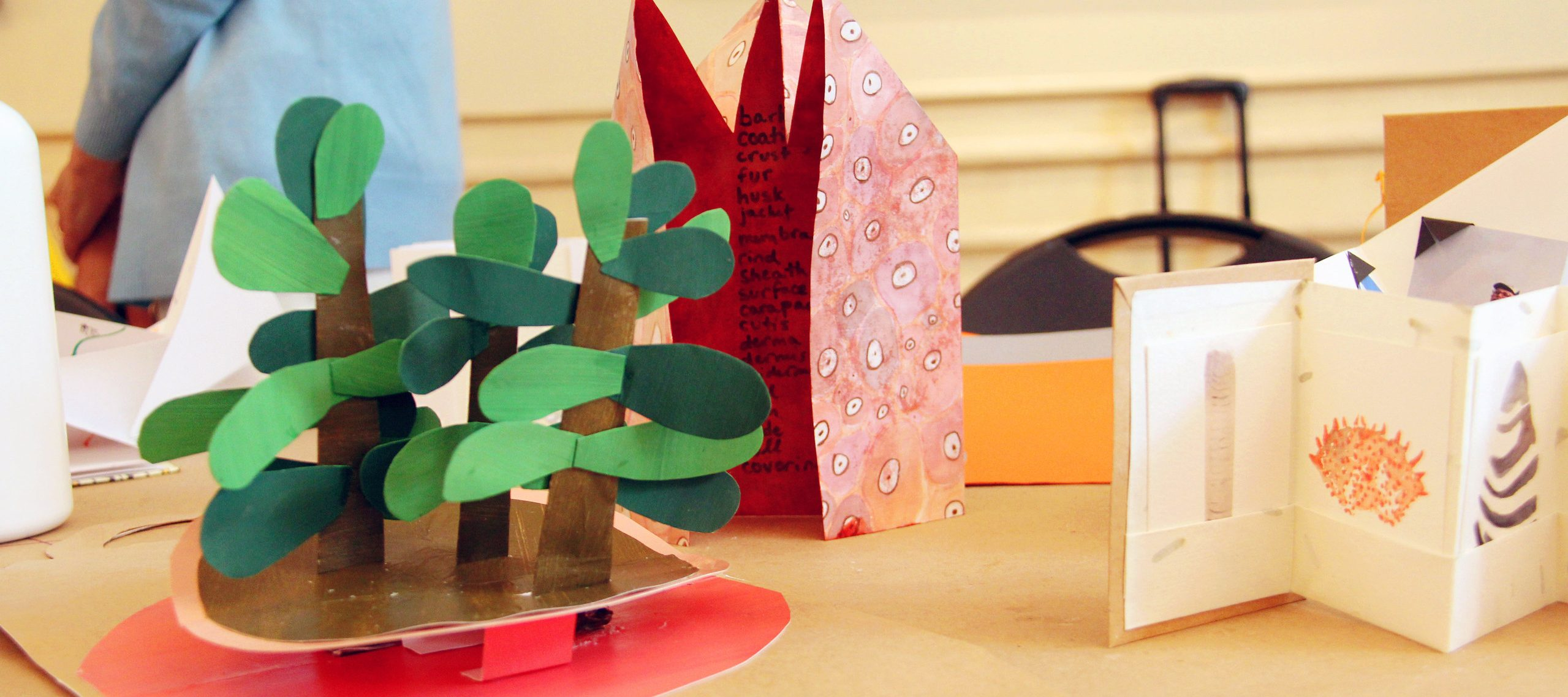 Folded paper books are displayed on a wood table.