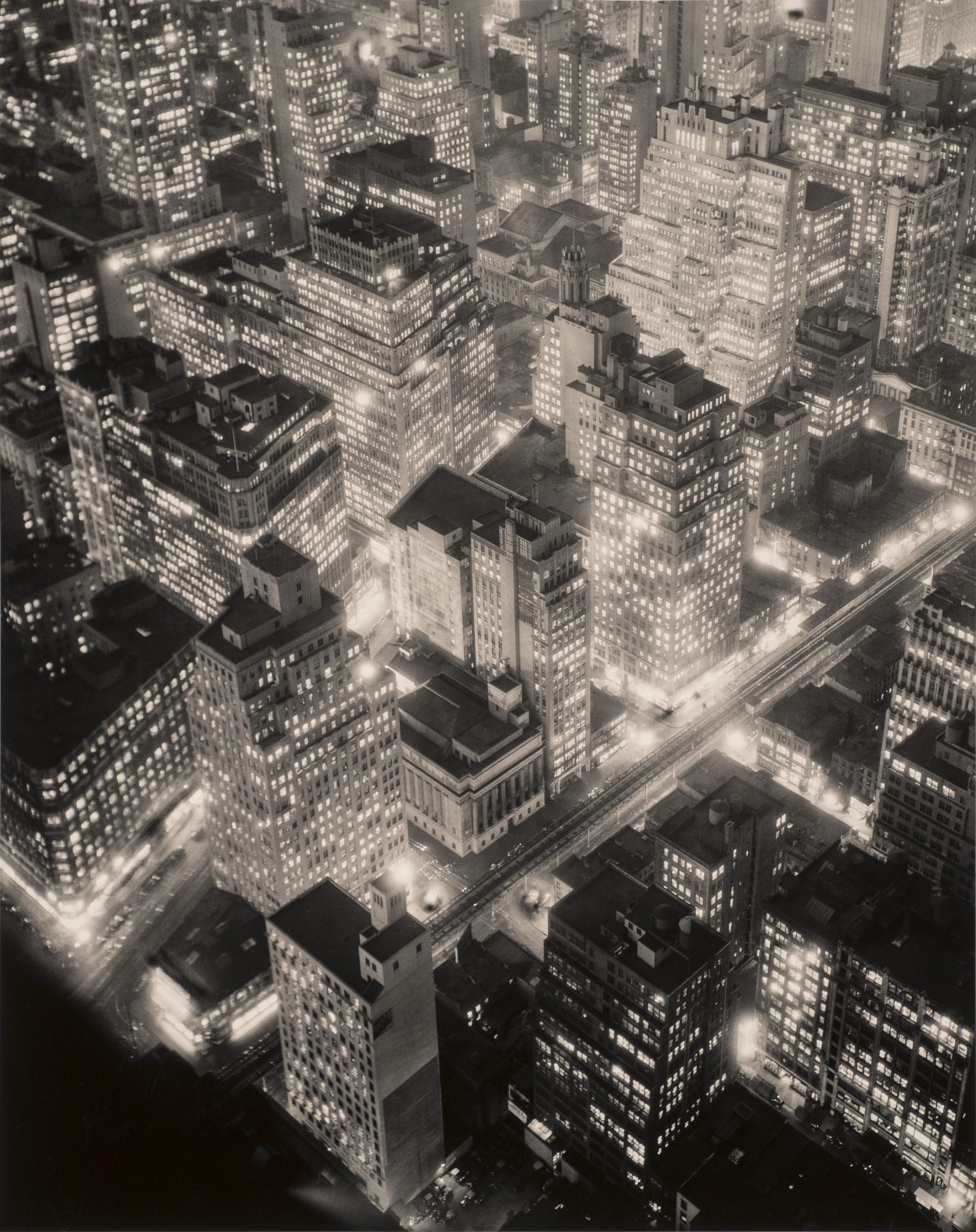 A black-and-white photograph of New York City seen from above at night. Towering, blocky skyscrapers emerge from the ground, glowing from tiny square windows of light, lining streets filled with blurs and flashes of light.