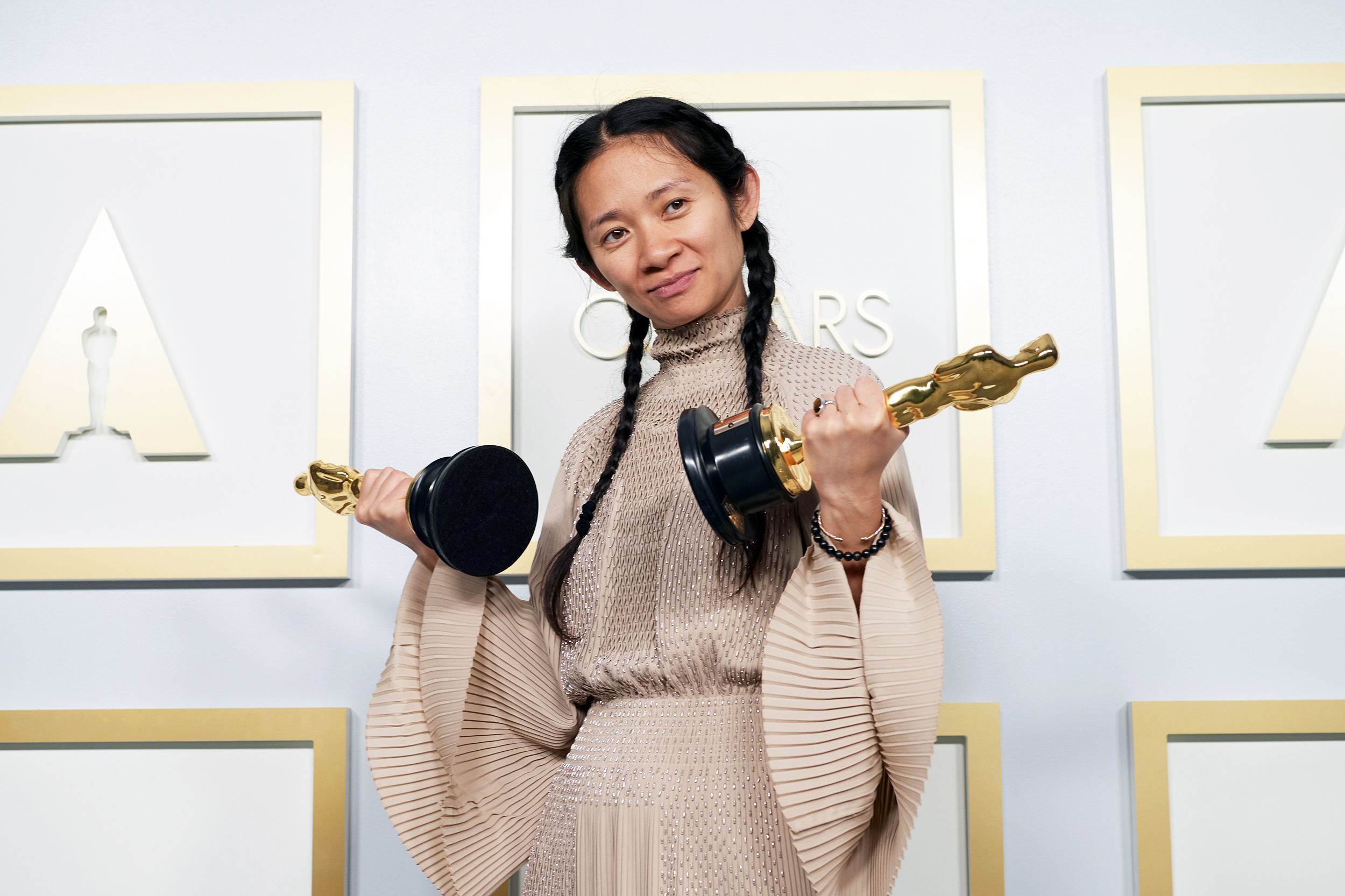 A medium-skinned woman of Asian descent holds two Oscar award statues in either hand, both pointed out to either side. She smiles slightly, her black hair is in two french braids, and she wears an earth-toned dress with fan sleeves.