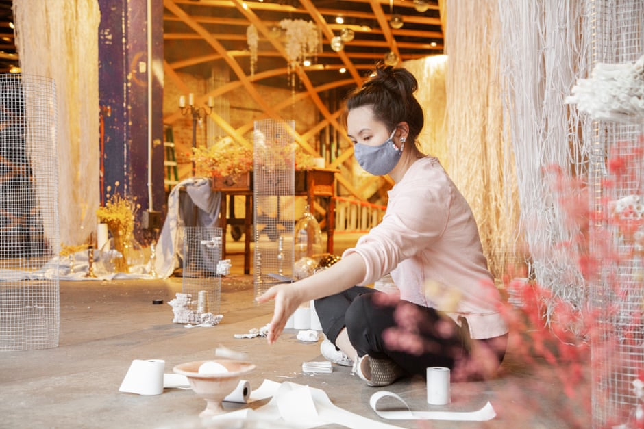 A light-skinned woman of Asian descent sits cross-legged on a concrete floor wearing a face mask, with a collection of detritus surrounding her, including rolls of toilet paper in different sizes, a clay bowl with an object in it, and others. Around and behind here textile works hang.