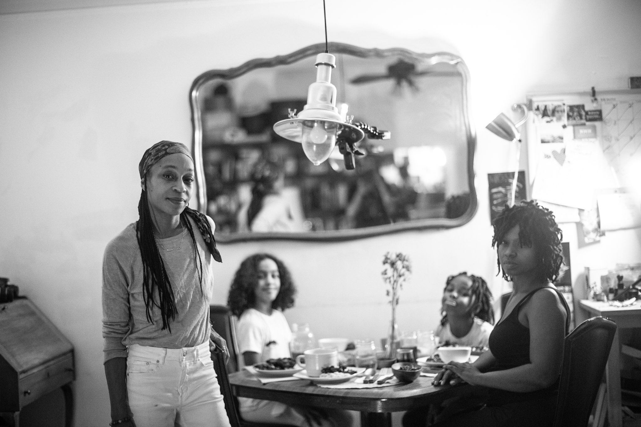 A black-and-white photograph of two women and two girls, all with medium-dark skin tones, together at a dining table set for dinner. A lamp hangs over the table and a mirror hangs on a wall behind them. The woman on the left is standing, while the other three sit at the table.